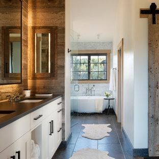 Modelo de cuarto de baño principal y abovedado, rústico, de tamaño medio, con armarios con paneles lisos, puertas de armario blancas, bañera exenta, ducha esquinera, paredes blancas, suelo gris, ducha con puerta con bisagras y encimeras negras