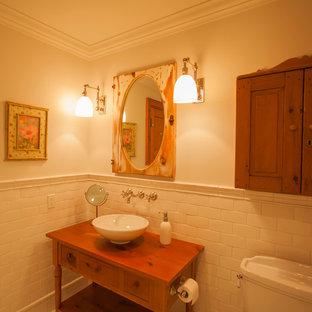 トロントのトラディショナルスタイルのおしゃれな浴室 (壁付け型シンク、オープンシェルフ、中間色木目調キャビネット、亜鉛の洗面台、猫足浴槽、一体型トイレ、白いタイル、磁器タイル、白い壁、無垢フローリング) の写真
