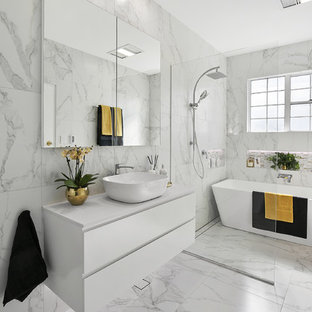 Inspiration for a large contemporary master wet room bathroom in Sydney with white cabinets, a freestanding tub, ceramic tile, white walls, ceramic floors, a vessel sink, marble benchtops, white floor, an open shower, white benchtops, flat-panel cabinets, gray tile and white tile.