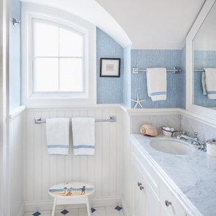 Maritimes Kinderbad mit Unterbauwaschbecken, Schrankfronten mit vertiefter Füllung, weißen Schränken, weißen Fliesen, blauer Wandfarbe, buntem Boden und grauer Waschtischplatte in Portland Maine