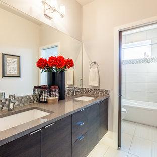 Modelo de cuarto de baño minimalista, pequeño, con armarios con paneles lisos, puertas de armario de madera en tonos medios, bañera empotrada, combinación de ducha y bañera, sanitario de una pieza, baldosas y/o azulejos negros, baldosas y/o azulejos blancas y negros, baldosas y/o azulejos grises, baldosas y/o azulejos blancos, baldosas y/o azulejos en mosaico, paredes blancas, suelo vinílico, lavabo sobreencimera y encimera de terrazo