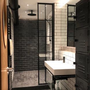 Mittelgroßes Industrial Duschbad mit Duschnische, Metrofliesen, schwarzem Boden, offenen Schränken, schwarzen Schränken, schwarz-weißen Fliesen, Wandwaschbecken, offener Dusche und Zementfliesen in London