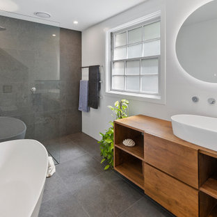 Mid-sized contemporary master bathroom in Sydney with a freestanding tub, porcelain tile, white walls, porcelain floors, a vessel sink, wood benchtops, grey floor, an open shower, flat-panel cabinets, medium wood cabinets, a curbless shower, gray tile and brown benchtops.