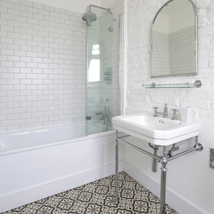 Medium sized mediterranean bathroom in London with a shower/bath combination, ceramic flooring, a console sink, metro tiles, white walls and black and white tiles.