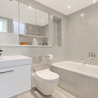 Foto de cuarto de baño principal, actual, de tamaño medio, con armarios con paneles lisos, puertas de armario blancas, bañera esquinera, sanitario de pared, baldosas y/o azulejos grises, paredes grises, suelo gris y lavabo integrado