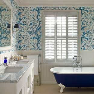 Design ideas for a classic ensuite bathroom in London with recessed-panel cabinets, white cabinets, a freestanding bath, blue walls and a built-in sink.
