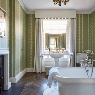 Inspiration for a classic bathroom in London with a freestanding bath, green walls, medium hardwood flooring, a pedestal sink and brown floors.