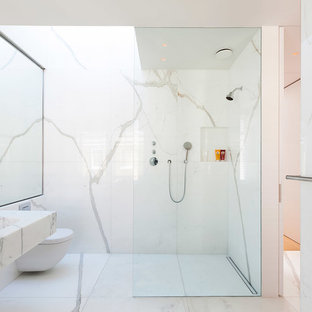 Mid-sized contemporary 3/4 bathroom in London with a wall-mount toilet, marble, white walls, marble floors, a wall-mount sink, white floor, a corner shower, black and white tile, marble benchtops, an open shower and a niche.