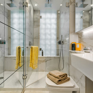 Photo of a medium sized contemporary shower room bathroom in London with an alcove shower, a wall mounted toilet, grey tiles, a trough sink, beige floors and a hinged door.