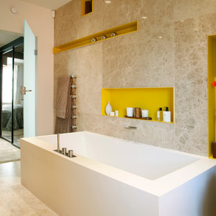 Freestanding bathtub - mid-sized contemporary master beige tile freestanding bathtub idea in London with yellow cabinets and beige walls