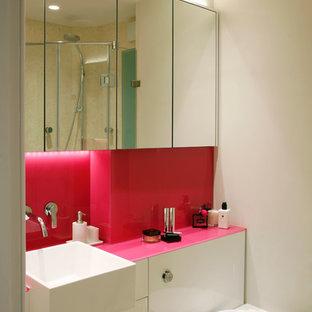 Inspiration pour une salle de bain design avec des portes de placard blanches, un placard à porte plane, un mur blanc et un plan de toilette rose.
