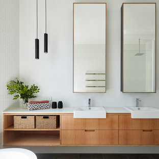 This is an example of a mid-sized contemporary master bathroom in Adelaide with open cabinets, light wood cabinets, a freestanding tub, a one-piece toilet, white tile, ceramic tile, white walls, ceramic floors, a drop-in sink, grey floor, an open shower, white benchtops, a double vanity, an open shower, engineered quartz benchtops and a floating vanity.