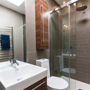 Photo of a contemporary bathroom in London with an alcove shower and grey tiles.