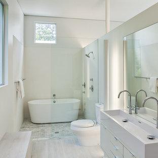 Diseño de cuarto de baño principal, moderno, de tamaño medio, con armarios con paneles lisos, puertas de armario blancas, bañera exenta, combinación de ducha y bañera, sanitario de dos piezas, baldosas y/o azulejos multicolor, baldosas y/o azulejos de cemento, paredes blancas, suelo de bambú, lavabo suspendido y encimera de acrílico