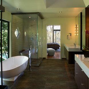 Imagen de cuarto de baño principal, de estilo zen, con armarios con paneles lisos, puertas de armario de madera en tonos medios, bañera exenta, ducha empotrada, suelo de baldosas de porcelana, lavabo integrado, encimera de cuarcita y ducha con puerta con bisagras