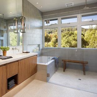 Esempio di una stanza da bagno padronale contemporanea con ante lisce, ante in legno scuro, vasca da incasso, doccia a filo pavimento, WC monopezzo, piastrelle grigie, piastrelle di vetro, pavimento con piastrelle in ceramica, lavabo sottopiano e top in marmo
