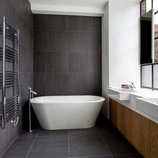 Design ideas for an urban bathroom in London with a vessel sink, flat-panel cabinets, medium wood cabinets, a freestanding bath, grey tiles and white walls.