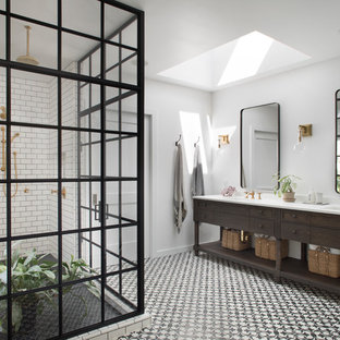 Photo of a country bathroom in San Francisco with furniture-like cabinets, dark wood cabinets, a corner shower, white tile, subway tile, white walls, an undermount sink and a hinged shower door.