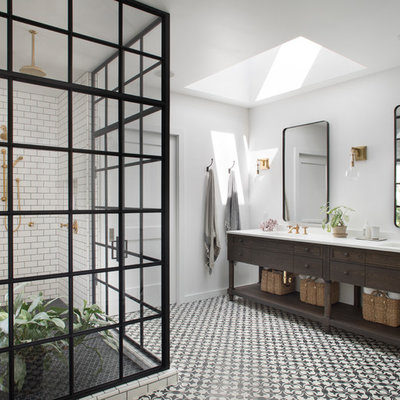 Example of a country white tile and subway tile corner shower design in San Francisco with furniture-like cabinets, dark wood cabinets, white walls, an undermount sink and a hinged shower door