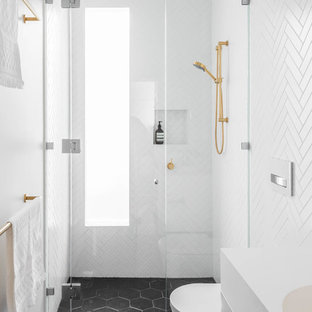 Contemporary 3/4 bathroom in Melbourne with flat-panel cabinets, white cabinets, an alcove shower, a one-piece toilet, white tile, white walls, an integrated sink, black floor, a hinged shower door and white benchtops.
