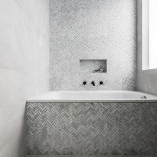 Réalisation d'une salle de bain principale design de taille moyenne avec un placard à porte plane, des portes de placard en bois sombre, une baignoire posée, un WC à poser, un carrelage gris, des carreaux de porcelaine, un mur gris, un sol en carrelage de porcelaine, un lavabo intégré, un plan de toilette en surface solide, un sol gris, un espace douche bain et une cabine de douche à porte battante.