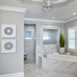 Diseño de cuarto de baño principal, exótico, grande, con armarios estilo shaker, puertas de armario blancas, bañera encastrada, ducha a ras de suelo, paredes grises, suelo de mármol, lavabo bajoencimera, encimera de terrazo, ducha abierta y suelo blanco