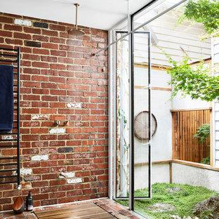 На фото: ванная комната в современном стиле с душем без бортиков, красными стенами, кирпичным полом и открытым душем с