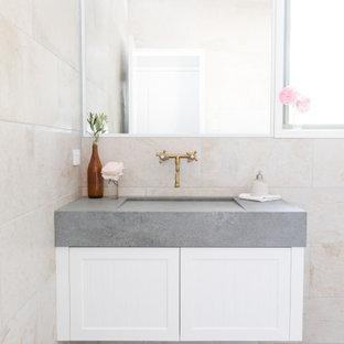 Esempio di una stanza da bagno per bambini country di medie dimensioni con ante in stile shaker, ante bianche, piastrelle beige, piastrelle di pietra calcarea, top in cemento, un lavabo e mobile bagno sospeso
