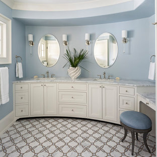 Inspiration for a coastal master marble floor and multicolored floor bathroom remodel in Charleston with recessed-panel cabinets, beige cabinets, blue walls, an undermount sink and gray countertops