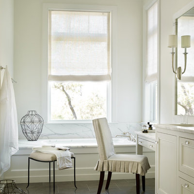 Example of a beach style white tile and stone tile drop-in bathtub design in Atlanta with shaker cabinets, white cabinets and white walls