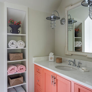 チャールストンのビーチスタイルのおしゃれな浴室 (落し込みパネル扉のキャビネット、オレンジのキャビネット、白い壁、アンダーカウンター洗面器、白い床、白い洗面カウンター、洗面台1つ、造り付け洗面台、三角天井) の写真