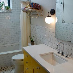 シカゴのインダストリアルスタイルのおしゃれな子供用バスルーム (フラットパネル扉のキャビネット、黄色いキャビネット、アンダーマウント型浴槽、一体型トイレ、白いタイル、セラミックタイル、白い壁、セラミックタイルの床、アンダーカウンター洗面器、人工大理石カウンター、白い床、開き戸のシャワー、白い洗面カウンター) の写真