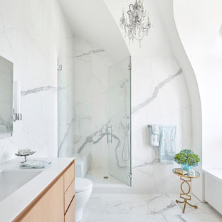 Alcove shower - large contemporary white tile white floor alcove shower idea in Chicago with flat-panel cabinets, light wood cabinets, an undermount sink, solid surface countertops, a hinged shower door and white walls
