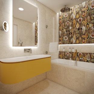 Immagine di una stanza da bagno per bambini minimalista di medie dimensioni con ante gialle, vasca ad alcova, vasca/doccia, piastrelle multicolore, top in vetro, ante lisce, piastrelle in travertino, pareti multicolore, pavimento in travertino, lavabo a consolle, pavimento beige e porta doccia a battente