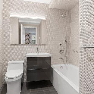 Idee per una piccola stanza da bagno con doccia contemporanea con vasca ad alcova, pavimento in gres porcellanato, ante lisce, ante grigie, doccia alcova, WC monopezzo, piastrelle beige, piastrelle a mosaico, pareti beige, lavabo da incasso e pavimento grigio