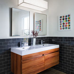 Example of a mid-sized trendy kids' subway tile and gray tile brown floor bathroom design in New York with flat-panel cabinets, medium tone wood cabinets, white walls, an integrated sink, white countertops and quartz countertops
