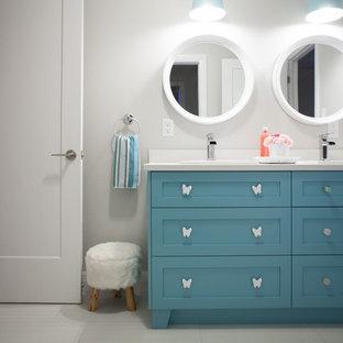 Aménagement d'une grande salle de bain craftsman pour enfant avec un placard à porte shaker, des portes de placard turquoises, une baignoire en alcôve, un combiné douche/baignoire, un WC à poser, un carrelage multicolore, des carreaux de céramique, un mur gris, un sol en carrelage de céramique, un lavabo posé, un plan de toilette en carrelage et un sol blanc.