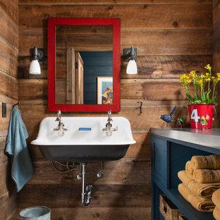 Rustik inredning av ett badrum för barn, med öppna hyllor, blå skåp, bruna väggar, ett avlångt handfat, bänkskiva i rostfritt stål och grått golv