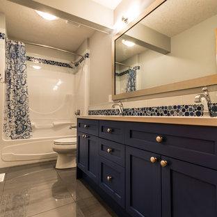 Esempio di una stanza da bagno classica di medie dimensioni con lavabo sottopiano, ante in stile shaker, ante blu, top in quarzo composito, vasca ad alcova, vasca/doccia, WC a due pezzi, piastrelle blu, piastrelle di vetro, pareti grigie e pavimento in gres porcellanato