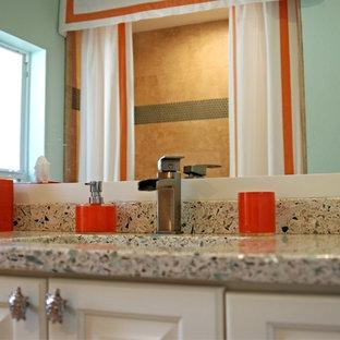 Ejemplo de cuarto de baño tradicional renovado con armarios con paneles con relieve, encimera de vidrio reciclado, baldosas y/o azulejos de vidrio y suelo de travertino