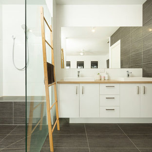 Contemporary bathroom in Other with flat-panel cabinets, white cabinets, gray tile, a drop-in sink, wood benchtops, grey floor and beige benchtops.