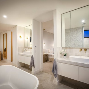 Design ideas for a contemporary master bathroom in Wollongong with raised-panel cabinets, white cabinets, a freestanding tub, gray tile, white walls, a vessel sink, grey floor and grey benchtops.