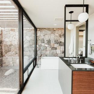 Идея дизайна: большая главная ванная комната в стиле фьюжн с плоскими фасадами, фасадами цвета дерева среднего тона, отдельно стоящей ванной, открытым душем, бежевой плиткой, каменной плиткой, бежевыми стенами, полом из керамогранита, врезной раковиной, столешницей из искусственного кварца, бежевым полом, открытым душем и черной столешницей