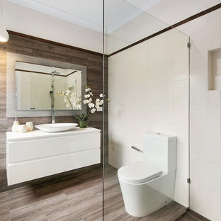 Photo of a contemporary 3/4 bathroom in Melbourne with flat-panel cabinets, white cabinets, an open shower, brown tile, white tile, white walls, a vessel sink, brown floor and an open shower.