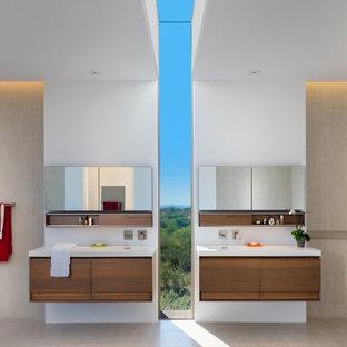 Modelo de cuarto de baño principal, contemporáneo, grande, con armarios con paneles lisos, encimera de cuarzo compacto, paredes blancas, suelo de baldosas de porcelana, puertas de armario de madera en tonos medios, baldosas y/o azulejos grises, baldosas y/o azulejos de porcelana, encimeras blancas, bañera exenta, sanitario de una pieza, lavabo integrado y suelo gris