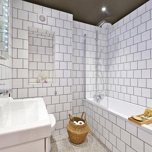 Mittelgroßes Modernes Kinderbad mit weißen Schränken, Duschbadewanne, Toilette mit Aufsatzspülkasten, weißen Fliesen, Keramikfliesen, weißer Wandfarbe, Terrazzo-Boden, grauem Boden, Falttür-Duschabtrennung und Eckbadewanne in London