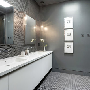 Inspiration for a contemporary bathroom in DC Metro with flat-panel cabinets, white cabinets, an alcove tub, a corner shower, porcelain tile, grey walls, an integrated sink, solid surface benchtops and black floor.