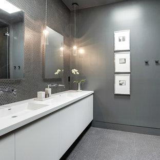 Ejemplo de cuarto de baño contemporáneo con armarios con paneles lisos, puertas de armario blancas, bañera empotrada, ducha esquinera, baldosas y/o azulejos de porcelana, paredes grises, lavabo integrado, encimera de acrílico, suelo negro, ducha con puerta con bisagras y encimeras blancas