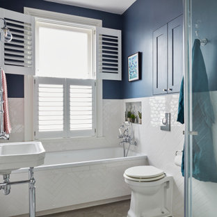 Inspiration for a small classic family bathroom in Kent with blue walls, grey floors, a built-in bath, a walk-in shower, a wall mounted toilet, white tiles, porcelain tiles, cement flooring, a hinged door, a single sink, a freestanding vanity unit and a console sink.