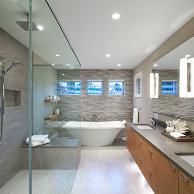 Large trendy master gray tile and porcelain tile porcelain tile and beige floor bathroom photo in Vancouver with flat-panel cabinets, medium tone wood cabinets, beige walls, an undermount sink, quartz countertops, a hinged shower door and gray countertops